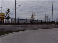 IRON EAGLE  FENCE ON RETAINING WALL